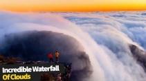 Захватывающий вид на водопад из облаков стекающих со склона горы